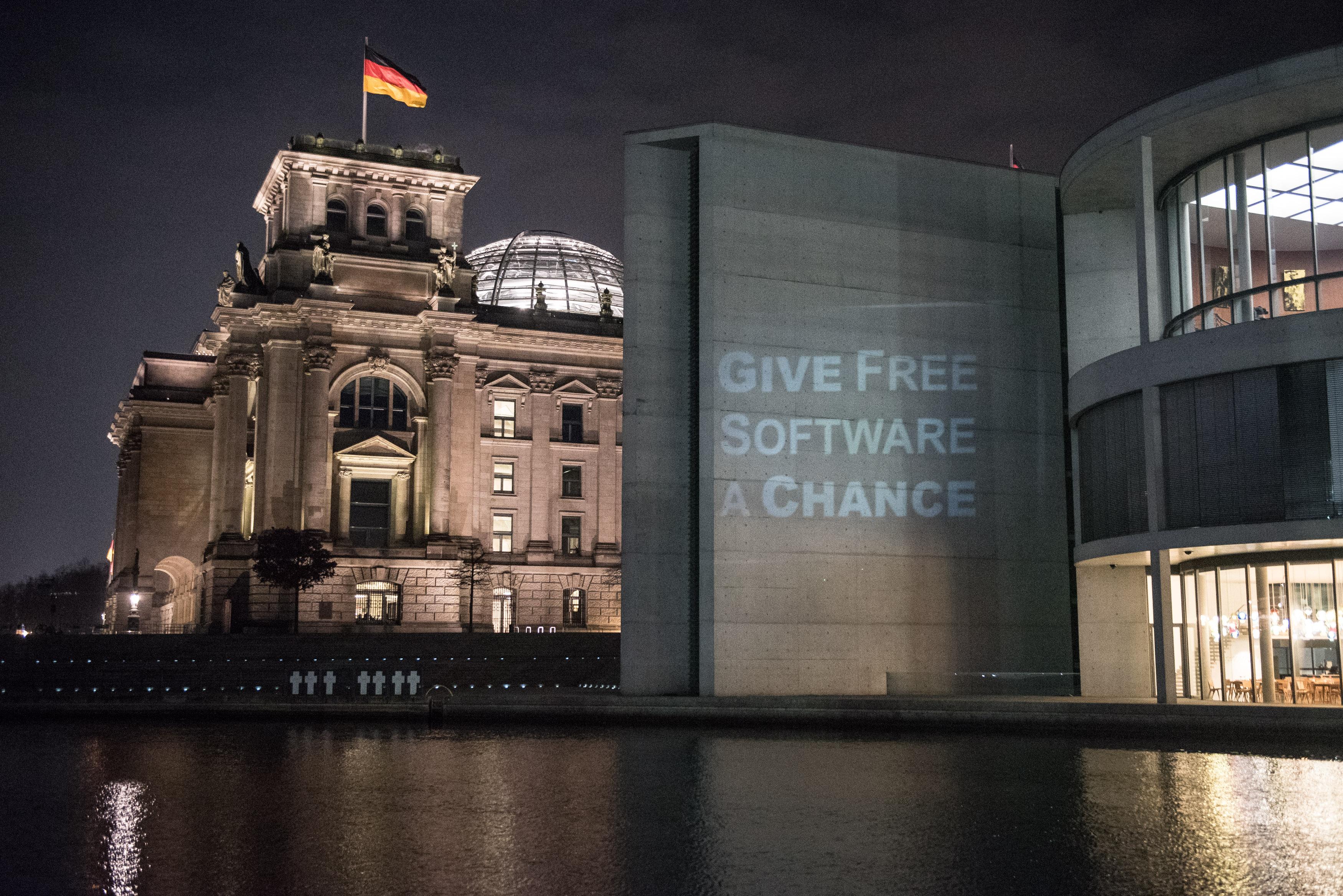 Il palazzo del Reichstag con la scritta 'Dai una chance al Software Libero' proiettata in primo piano