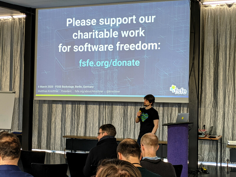 Matthias Kirschner gives his keynote about the core values of Software Freedom, the slide says Please support our charitable work for software freedom.