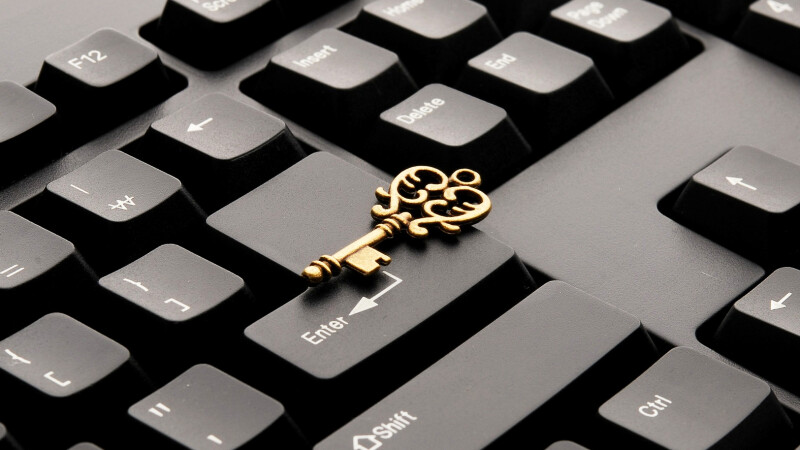 A golden key lying on the enter key of keyboard.