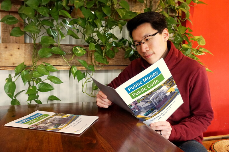 Interested reader with a Public Money Public Code brochure